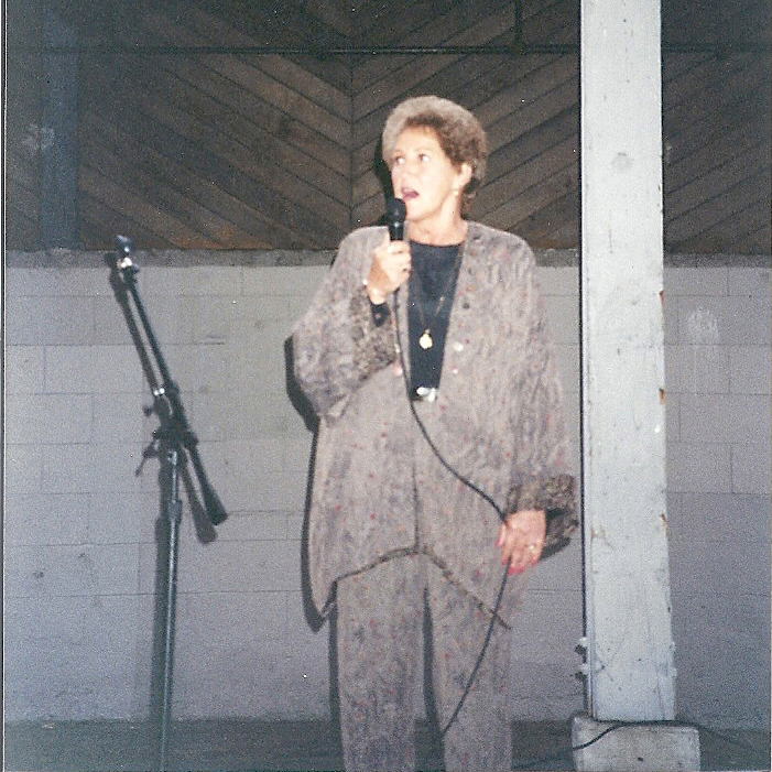 Nan Busby speaking to graduates at a ceremony.